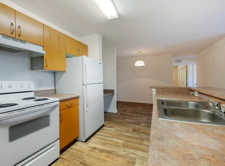 Kitchen with Wood Cabinets, Tan Counters and white Appliances, with view of dining room and built in desk in the background