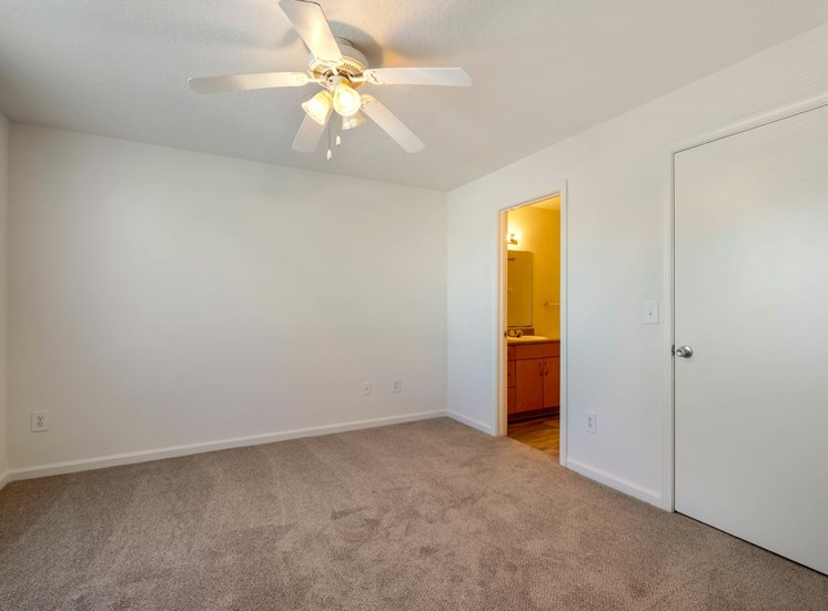 Carpeted Bedroom with white walls and ceiling fan, with view of bathroom