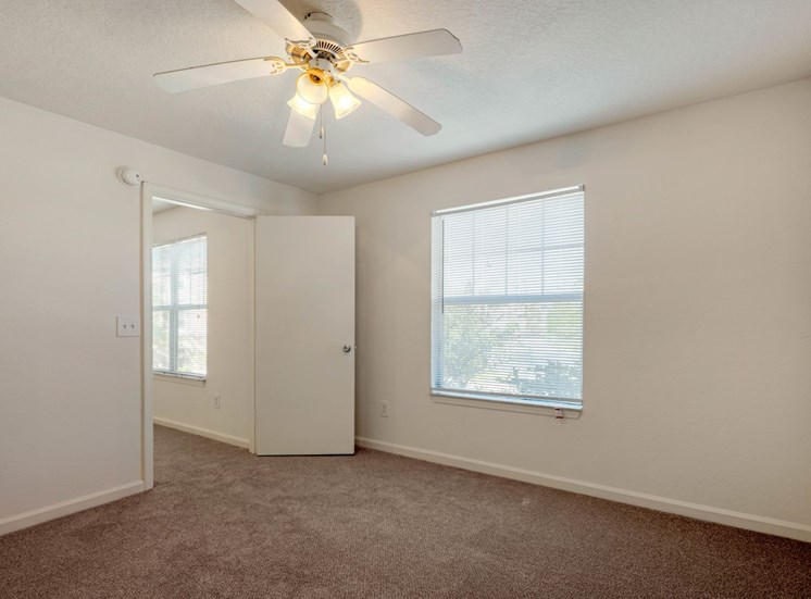 Carpeted Bedroom with white walls and one widow and ceiling fan