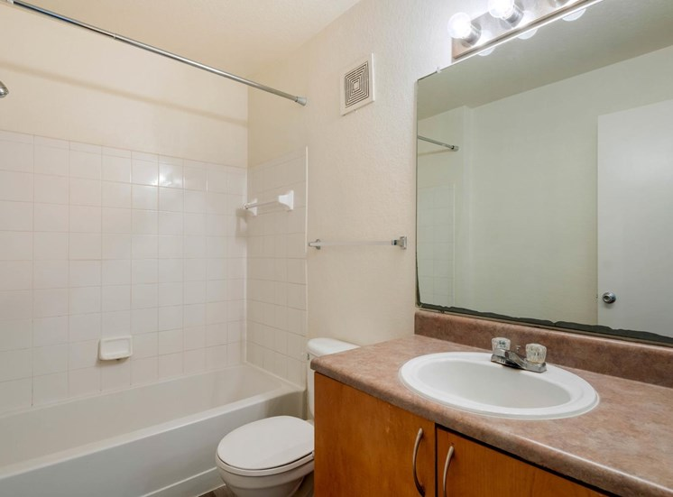 Bathroom with wood flooring, toilet, shower tub combo with tile back splash, towel bar, brown cabinets