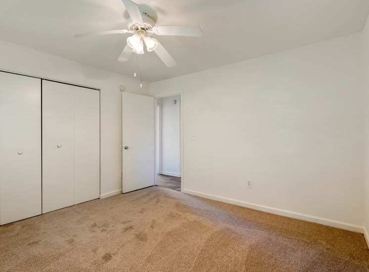 Carpeted Bedroom with white walls and one widow, double door closet, and ceiling fan