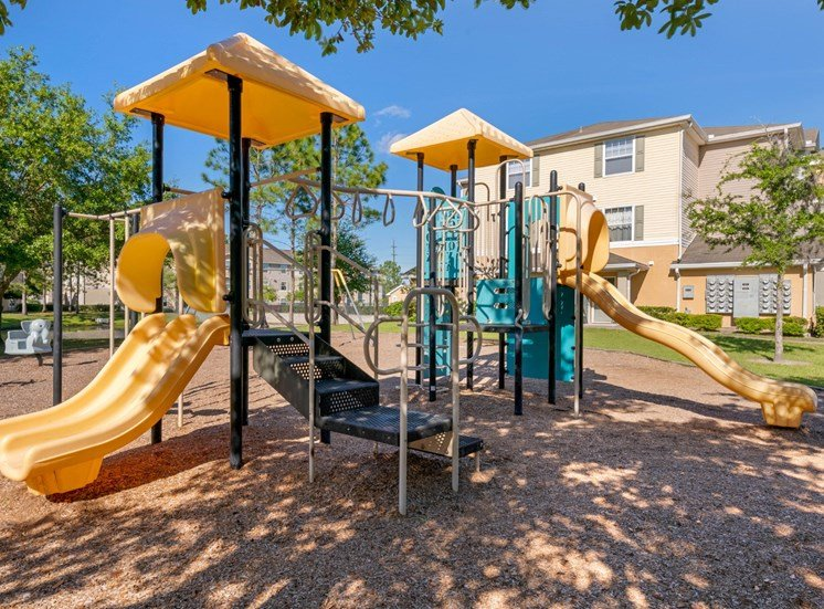 Playground jungle gym and playground slides in a bed of mulch with trees, and building exteriors in the background
