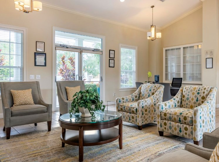 Clubhouse lounge with chairs, coffee table, rug, and pendant lighting