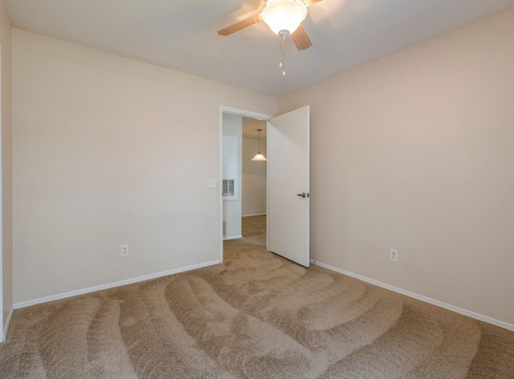 Spacious bedroom with carpet flooring and multi speed ceiling fan