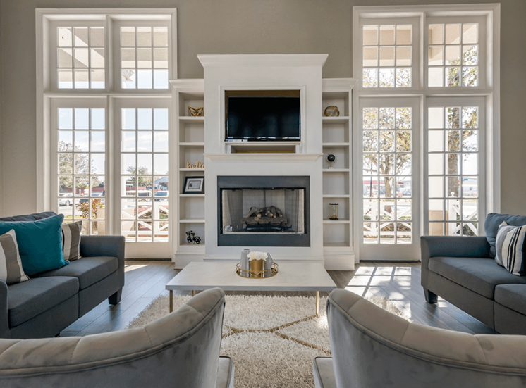 Clubhouse lounge with couches, chairs, coffee table, floor rug, fire place, and wall mounted television