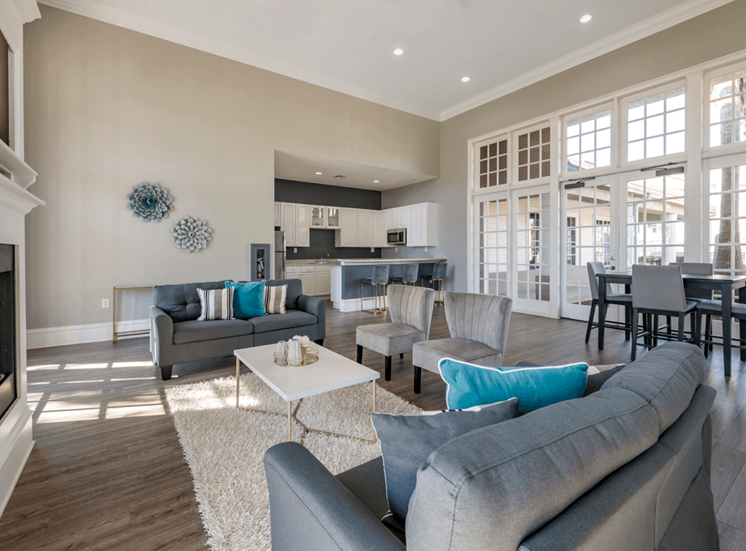 Clubhouse lounge with hardwood style flooring, floor rug, couch, chairs, coffee table, fire place, and large windows for natural lighting