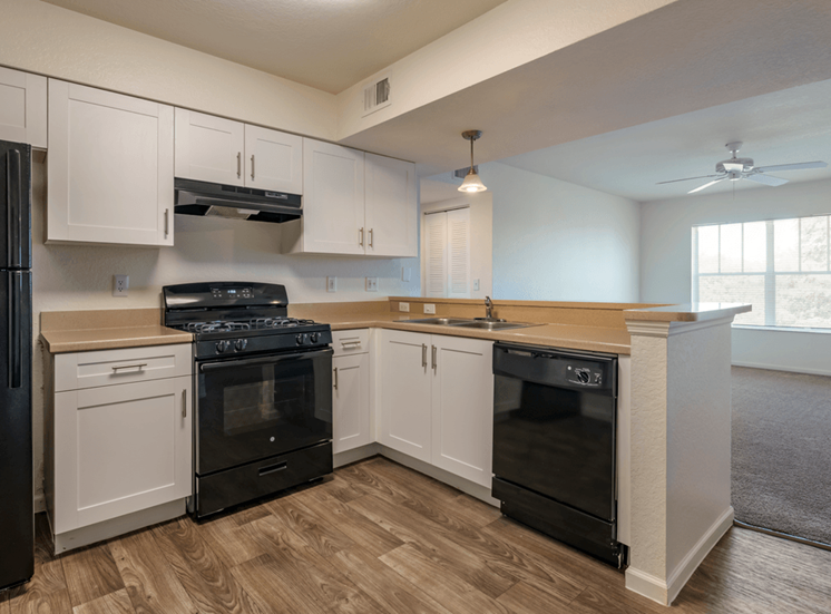 Kitchen with hardwood style flooring, whit cabinets, and black appliances