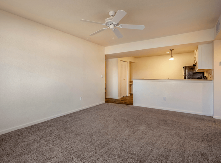 Spacious living room with carpet flooring, multi speed ceiling fan, and kitchen breakfast bar