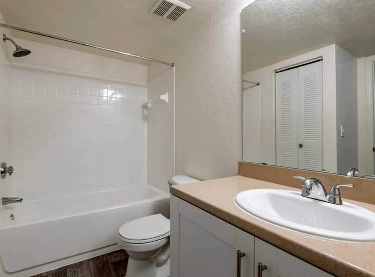 Bathroom with large mirror, vanity lighting, and tiled shower