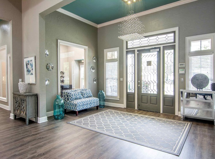 Leasing office interior entrance, with love seat, two cabinets, chandelier and decor