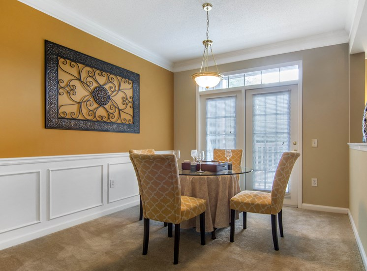 Furnished dining room with dining table four chairs and wall decor
