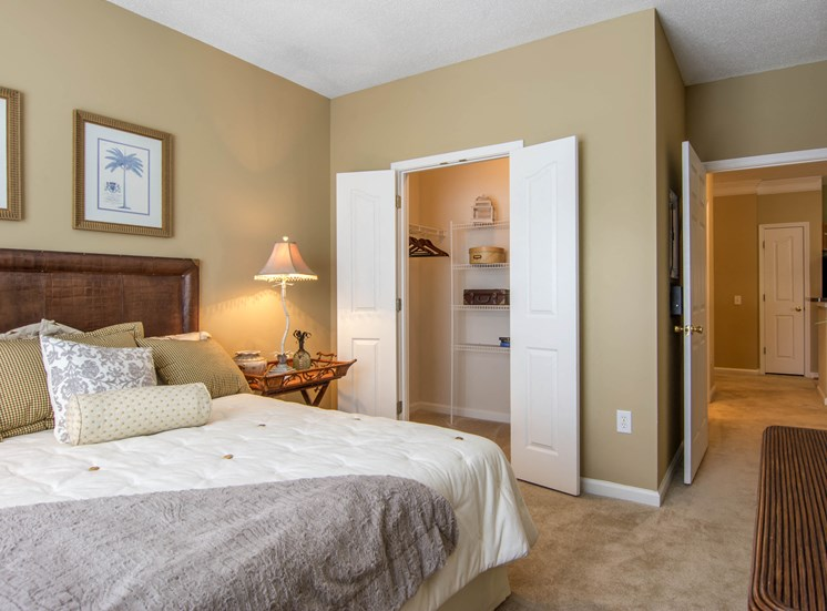 Furnished bedroom with large bed dresser and night stand