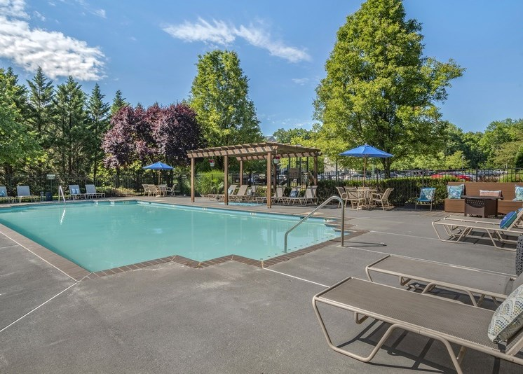 The community pool is rectangular in shape. The large sundeck area is enclosed with a black fence and features beige pool furniture including chaise lounge chairs, regular chairs, round tables, and blue umbrellas as well as a large wood-stained pergola. The exterior of the pool area is surrounded by bushes and mature trees. The community parking area is in the distance.