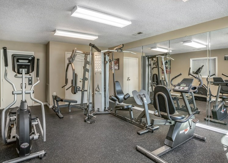 The community fitness center features several machines, including a chest press station, stationary bike, elliptical machine, and several cable exercise machines. The floor is a black rubberized surface, and the walls are beige throughout. One wall features floor-to-ceiling mirrors from end to end. Fluorescent lighting is featured throughout.