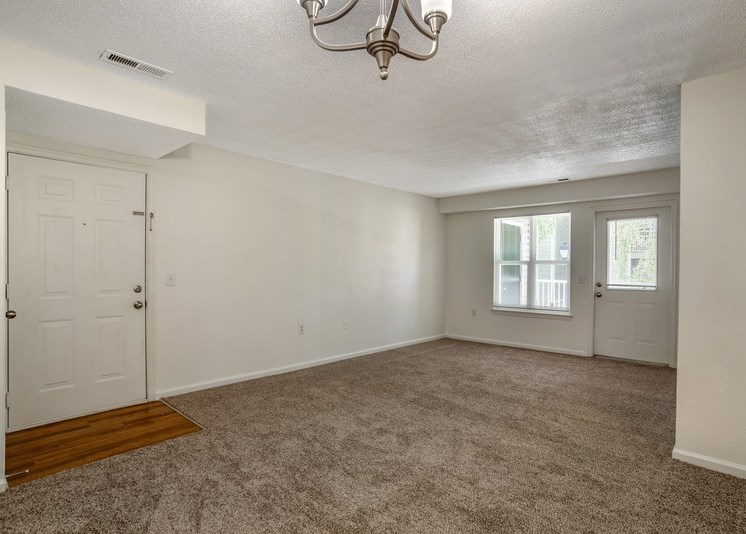 The entry door of the apartment on the left side of the room gives way to a hardwood-style landing and a spacious living area. The remaining flooring throughout the space features tan carpet. White walls lead up to a white textured ceiling. Windows and a patio door allow an ample amount of natural light into the living room. A chandelier is located on the ceiling at the near side of the room.