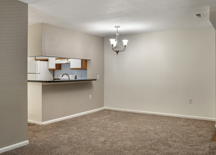 A vacant three-bedroom living room and dining room featuring white walls and white ceilings. The vinyl floor at the entry gives way to a carpeted living room and dining area with a chandelier providing light to the space. The kitchen is in the distance via a breakfast bar cut-out area that opens up to the dining room.