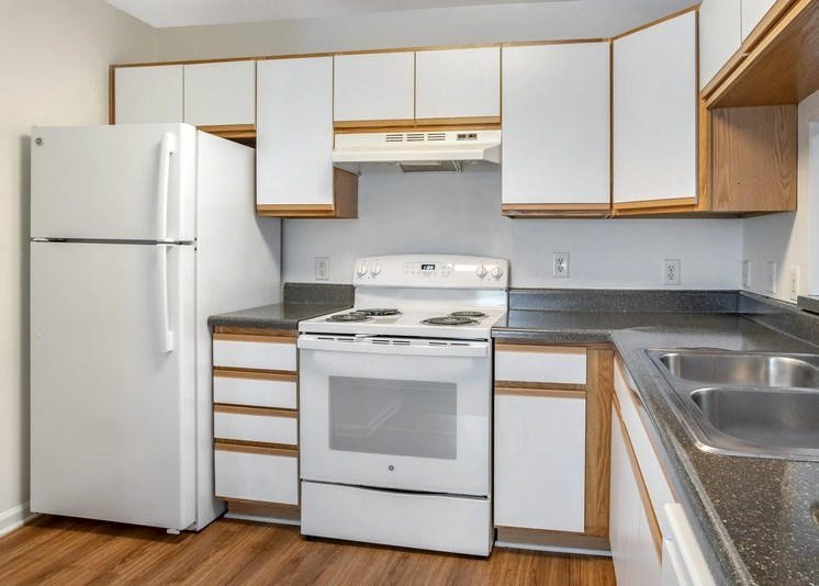 The vacant kitchen has white cabinets that feature natural wood-colored accents. Granite-style countertops throughout the space and a bar-top located just behind the stainless steel sink. Wood-style plank flooring throughout with white appliances including stove, oven, fridge, hood vent, and dishwasher.