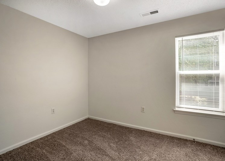 The vacant bedroom features tan carpet throughout with beige walls and a white textured ceiling. A window located on the right side of the room overlooks exterior trees. A rounded globe light sits in the center of the ceiling.