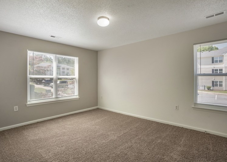 The vacant bedroom features tan carpet throughout with beige walls and a white textured ceiling. Windows are located on the right and left sides of the room providing ample natural light and feature blinds on both. A rounded globe light sits in the center of the ceiling.