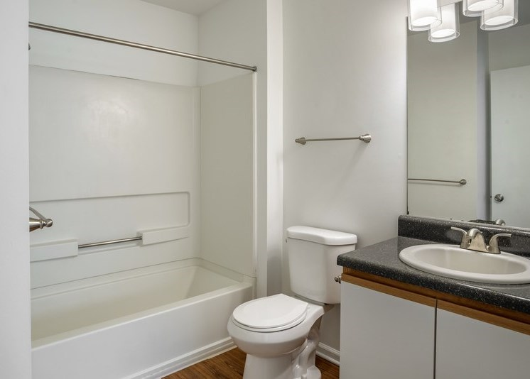 A vacant bathroom featuring white walls and a white ceiling. Brown wood-style flooring throughout. The bathroom also features a white shower/tub combo along with a black granite style bathroom vanity, white sink, and wood-colored trim surrounding the white cabinets.