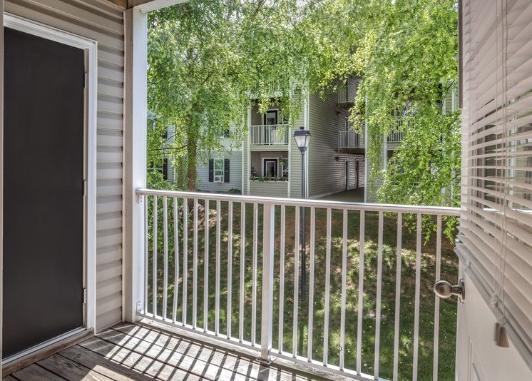 The large patio features wood decking and is enclosed by a white rod railing. There is a dark-colored door on the left side of the deck that leads to an exterior storage space. There are other apartment patios and mature trees located in the background.