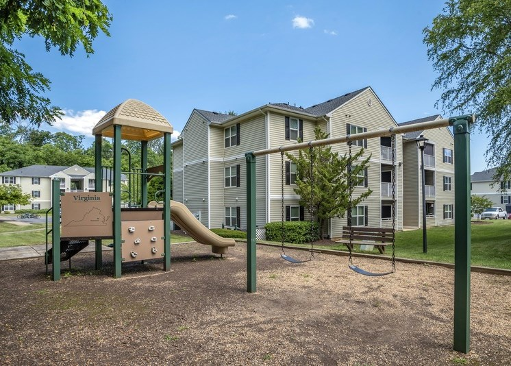 The community playground features a yellow, tan, and green play structure with a slide, a climbing wall, and two seated swings. The playground is surrounded by mulch, has a bench for seating, and sits adjacent to an apartment building in the background. There are mature trees in the foreground of the picture as well as in the distance beyond the apartment buildings.