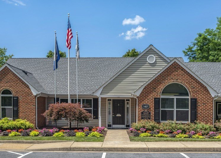 The leasing office has a sidewalk entry with a concrete ramp. It has a mulch bed in the front of the building with several bushes and flowers. The building is comprised of off-white siding and brick with several windows. The roof is comprised of dark shingles and mature trees fill the background against a blue sky. Multiple flag poles sit directly in front of the office.