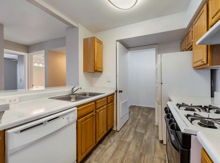 Kitchen with hardwood style flooring, double basin sink, white appliances, with gas stove range