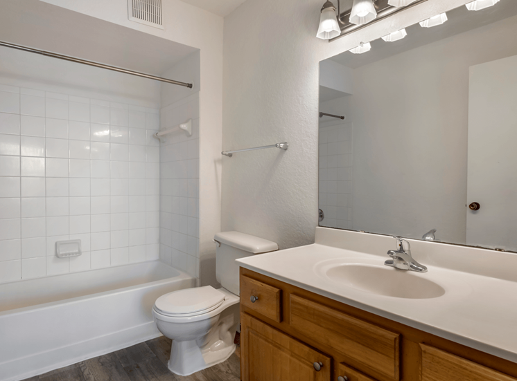 Bathroom with tiled shower and hardwood style flooring