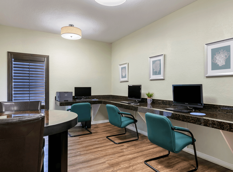 Business center with computers, desks, and hardwood style flooring