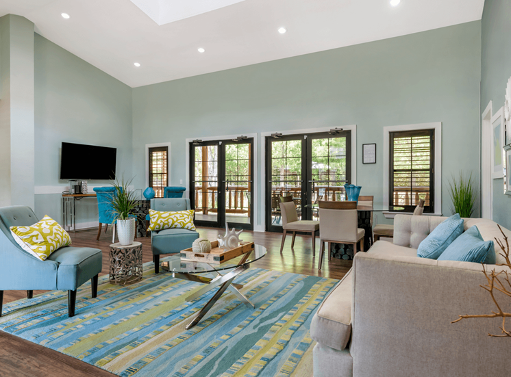 Clubhouse Lounge with couches, chairs, coffee table, television, and windows for natural lighting