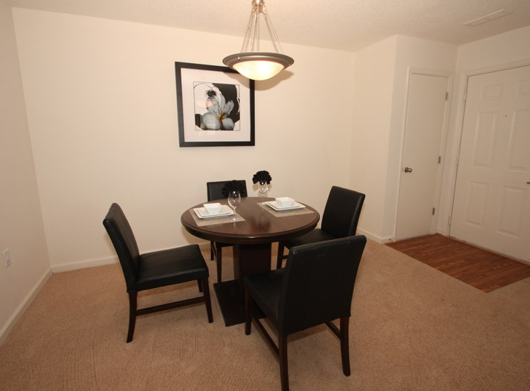 Dining room with a 4 person table and ceiling light above the table.