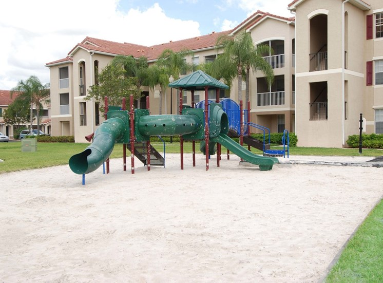 Playground on Sand in Courtyard Next to Buildings