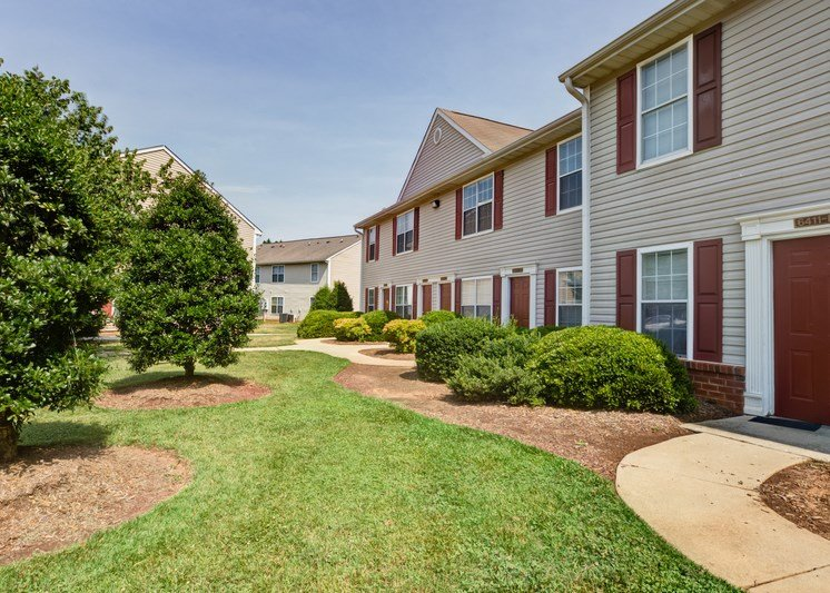 The apartment building exteriors are cream to tan in color with white trim and red shutters and doors. There are sidewalks leading to individual apartment doors, grass in areas between. the sidewalks, and large mature tree outside.