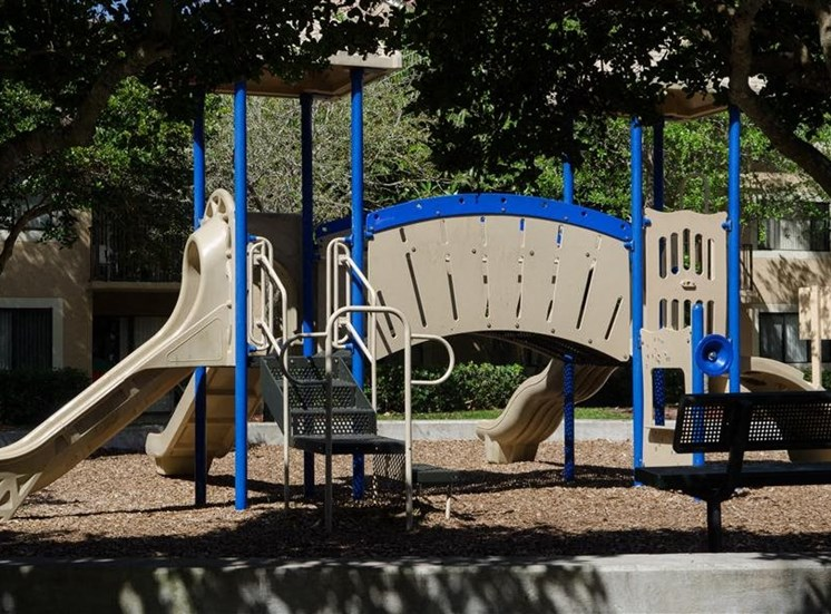 Blue and Beige Playground on Mulch Next to Trees