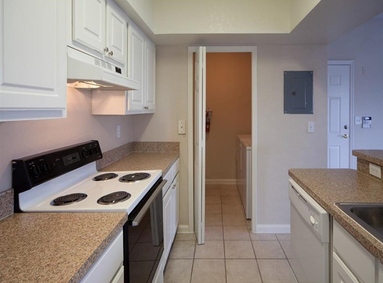 Kitchen with White Cabinets Beige Counters Double Sink and White Appliances and Utility Closet Door