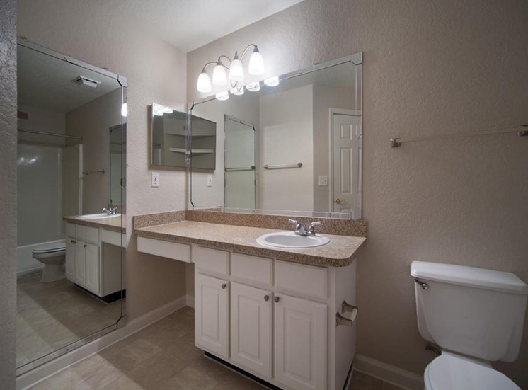 Bathroom with White Cabinets Beige Counters and Full Length Mirror