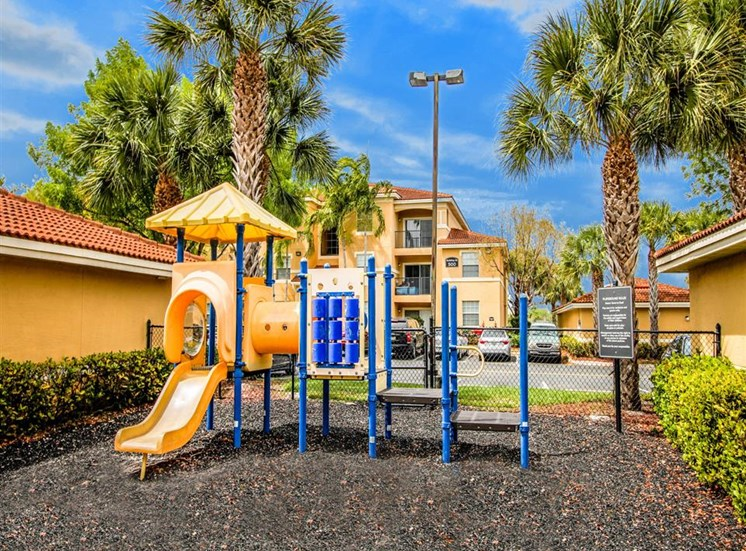 Multi Colored Playground on Mulch with Building Exterior in the Background