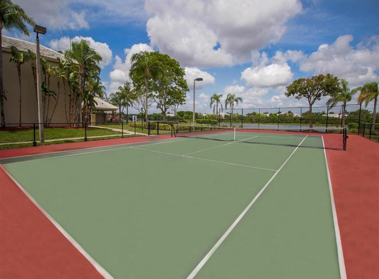 Fenced in Tennis Courts with Trees and Lights