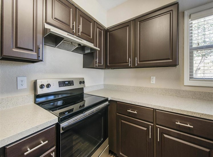 Kitchen with Brown Cabinets Stainless Steel Appliances and Grey Counters