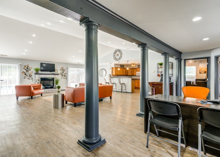 The interior of the Clubhouse/Leasing Office has hardwood style flooring, light gray walls with dark gray columns and trim. It is furnished with an orange couch, matching chair, area rug, a leasing desk with an orange chair and two black folding chairs. A kitchen area is located in the background.