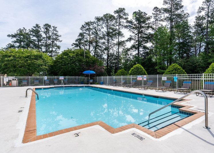The swimming pool is rectangular in shape surrounded by an expansive sundeck with gray and blue lounge chairs positioned throughout. There is a blue umbrella in the corner of the pool area. The entire pool area is fenced in and is surrounded by grass, trees, and bushes.