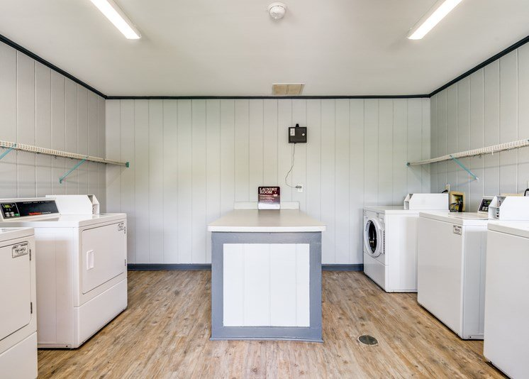 The Laundry Center has white walls and hardwood style flooring. It is equipped with multiple washers and dryers.