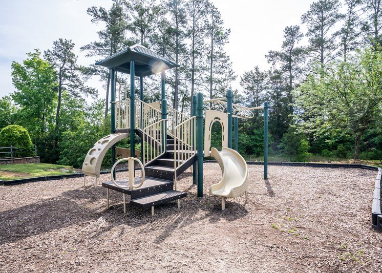 The community playground is surrounded by a large area of mulch, grass and trees. The play structure is green and tan with several climbing features, stairs and a single slide.
