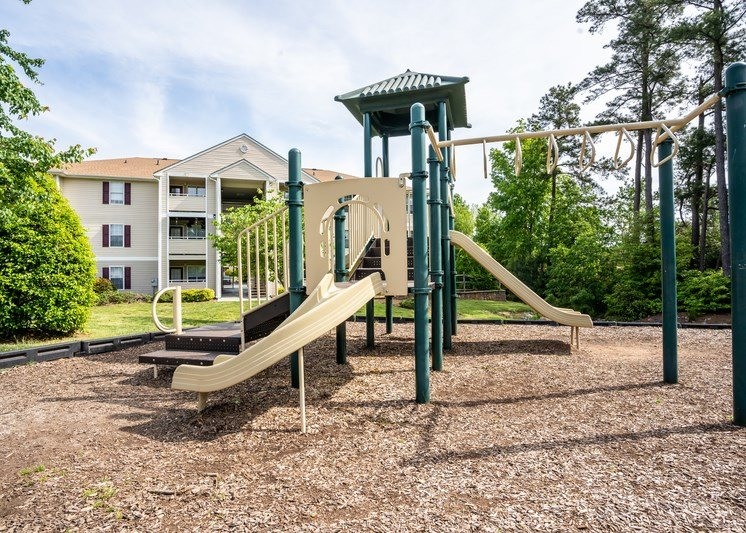 The community playground is surrounded by a large area of mulch, grass and trees. The play structure is green and tan with several climbing features, stairs and two single slides. An apartment building is located in t he background.