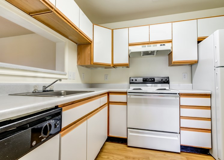 A vacant kitchen with hardwood style flooring, white walls, white cabinets with light wood trim, white appliances, light countertops, a single basin sink and a breakfast bar area located behind the sink. Appliances include a refrigerator, a stove/oven combo and a dishwasher.