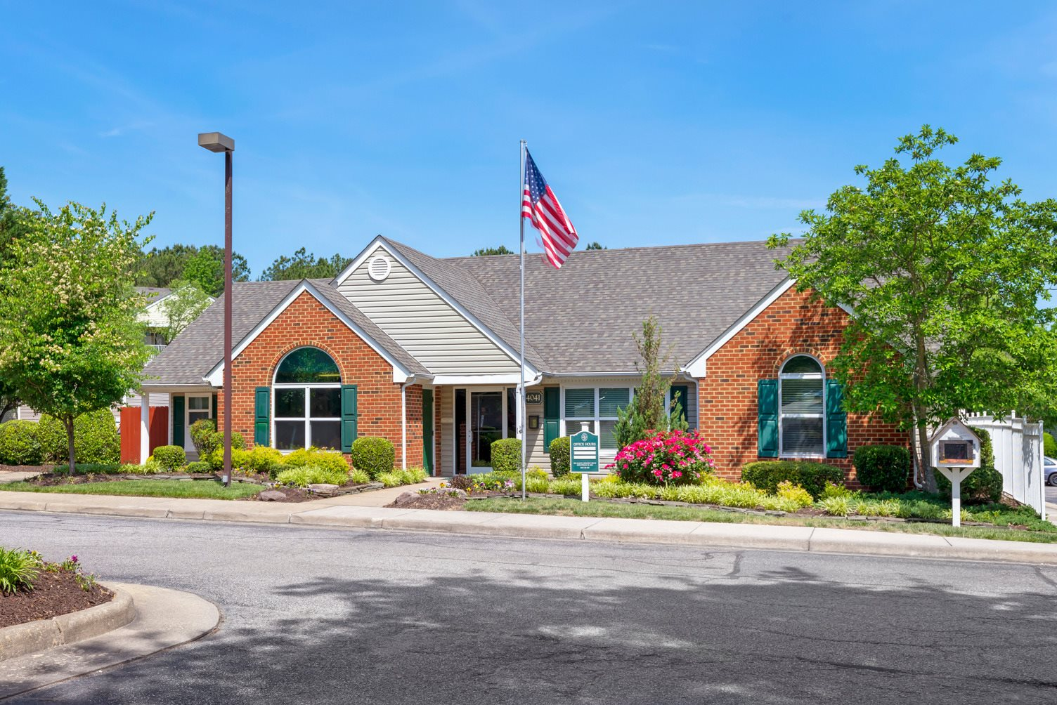Clubhouse exterior with flag pole, street light and parking lot.
