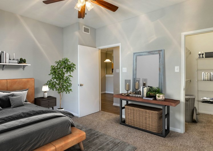 Bedroom with walk-in closet, ceiling fan, gray and tan color scheme, and a plant in the corner