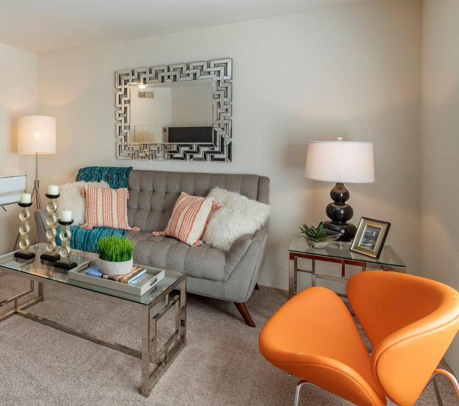 Furnished living room with sofa, orange accent chair, and view of kitchen with breakfast bar