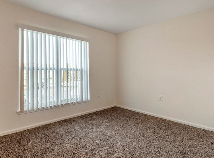 bedroom with a large window and carpet.